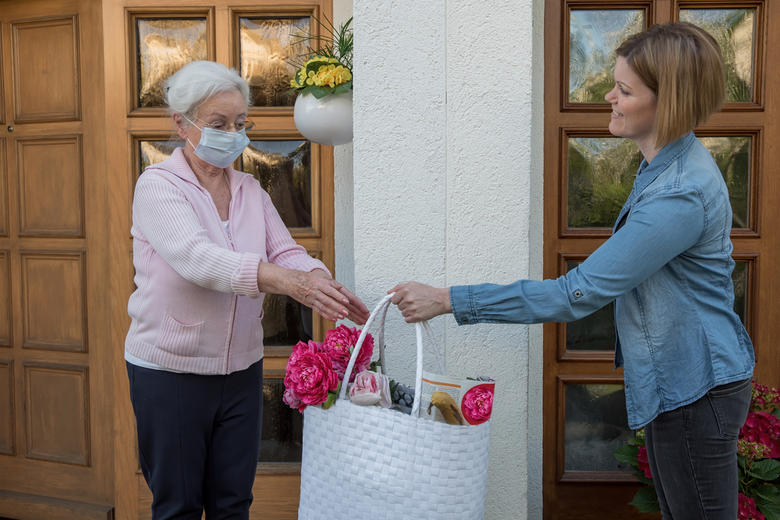 A woman with a face mask being handed a bag of food shopping from her neighbour