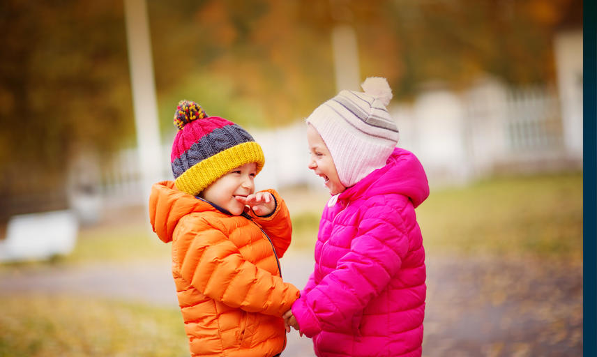 Two small children in orange and pink coats